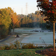 A worker mows the frost on a golf course early on a frosty fall morning.
