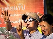 "02 JANUARY 2015 - KHLONG LUANG, PATHUM THANI, THAILAND: A woman cheers at Wat Phra Dhammakaya at the start of the 4th annual Dhammachai Dhutanaga (a dhutanga is a ""wandering"" and translated as pilgrimage). More than 1,100 monks are participating in a 450 kilometer (280 miles) long pilgrimage, which is going through six provinces in central Thailand. The purpose of the pilgrimage is to pay homage to the Buddha, preserve Buddhist culture, welcome the new year, and ""develop virtuous Buddhist youth leaders."" Wat Phra Dhammakaya is the largest Buddhist temple in Thailand and the center of the Dhammakaya movement, a Buddhist sect founded in the 1970s.   PHOTO BY JACK KURTZ"