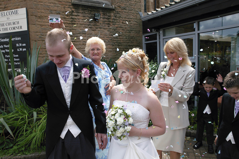 Guests throwing confetti over bride and groom outside church,