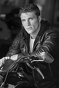 Hot man in a black leather jacket on a motorcycle in a garage
