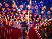 28 JANUARY 2017 - SAMUT PRAKAN, SAMUT PRAKAN, THAILAND: Thai-Chinese pray as they cross the celestial bridge into the shrine at the Chinese New Year Lantern Festival at the Tham Katanyu Foundation shrine in Samut Prakan, a suburb about 15 miles from Bangkok. More than 5,000 handmade lanterns imported from Taiwan are hung on the grounds of the shrine. Some of the lanterns are traditional Chinese lanterns, others are in the shapes of people or deities. There is also traditional Chinese entertainment, likes lion dances, at the festival.     PHOTO BY JACK KURTZ