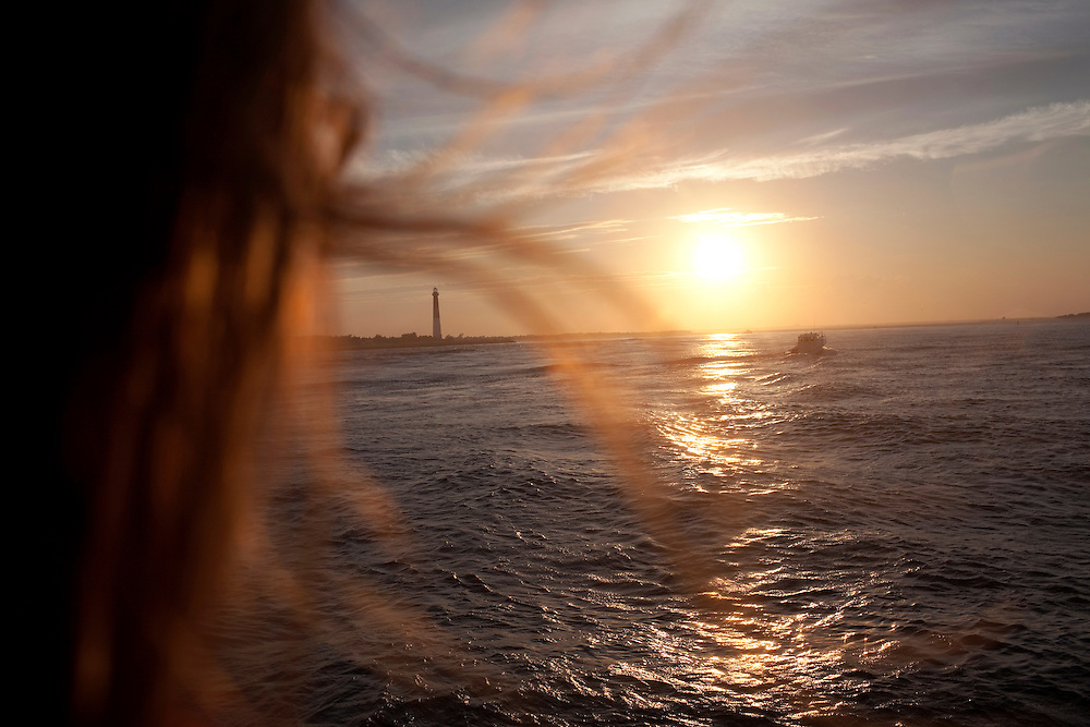 Long Beach Island, NJ - June 29, 2013 :  On Miss Barnegat Light sunset cruise, Katy Baker, 15, center, from Alsip, Il, watches the sun set over Barnegat Lighthouse, built in 1857, on the northern tip of Long Beach Island, NJ on June 29, 2013. Katy was part of a Lutheran church mission group visiting Long Beach Island to help with the post Hurricane Sandy clean up. People are returning to the beaches for the summer after recovery efforts post Superstorm Sandy.