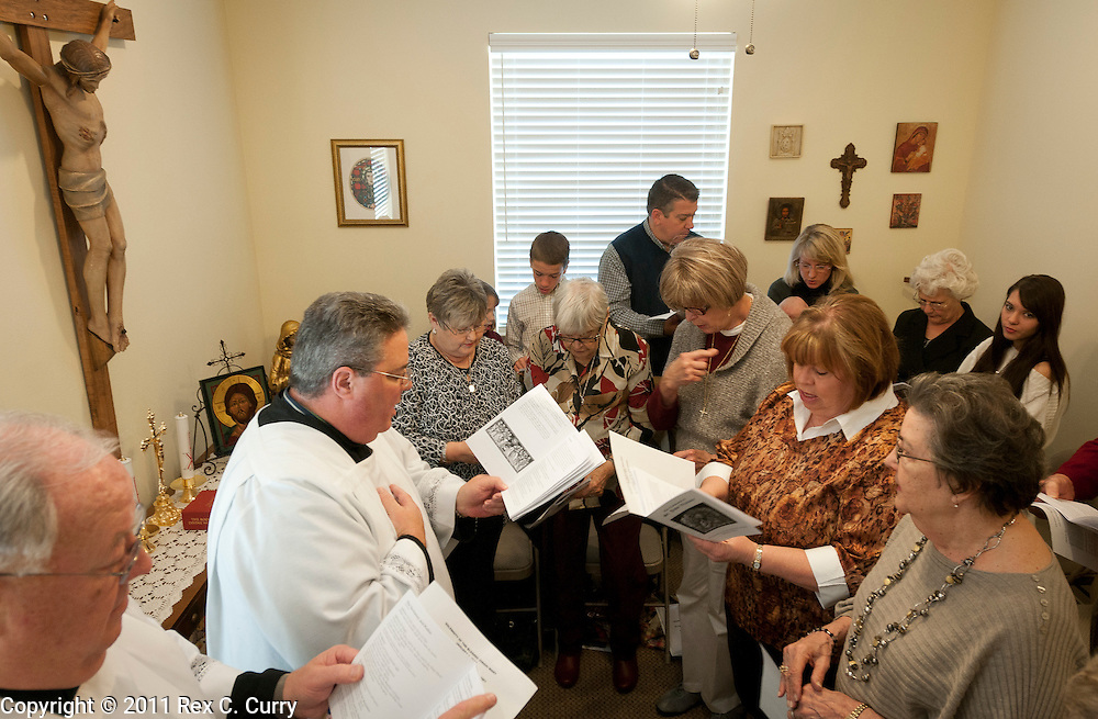 Father Charles Hough, second from left, leads his congregation in morning prayer at the St. John Vianney Parish in Cleburne, Tx. Sunday Jan. 1, 2012.  Hough is an Episcopal priest in the process of becoming ordained as a Catholic priest.  The parish is temporarily operating out of a private business..