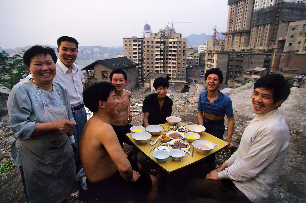 Labourers having dinner at a cheap restaurant, with a temporary, but dramatic view of this rapidly changing in-land metropolis high up on the Yangtze River, upstream from the Three Gorges Dam. ..From China [sur]real © Mark Henley..