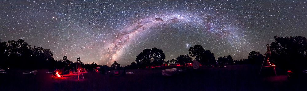 A 360&deg; panorama of the OzSky Star Safari 2014, at the Warrumbungles Mountain Motel near Coonabarabran, NSW, Australia, taken April 1 2014. The centre of the Galaxy area in Scorpius and Sagittarius is rising just left of centre (east); the Southern Cross and Carina Nebula area is at the peak of the arch of the Milky Way, at their highest for the night (south); Canis Major is setting at right (west). The Magellanic Clouds are above the trees at centre. At upper left is Mars, a week away from opposition. The Gegenschein is visible as a diffuse glow just left of Mars, the brightest part of the Zodiacal Band which runs from the Milky Way and Antares up tp Mars then off the frame at upper left. The Dark Emu figure made of dark clouds in the Milky Way is almost all above the horizon with his head in the Coal Sack at top centre, and his neck and bodt running down the Milky Way to the left toward the horizon. <br /> <br /> This is a 6-section panorama with the Canon 60Da at ISO 3200 and 60 second exposures, untracked, with the 8mm fish-eye lens at f/3.5. Lighting and movement between segments produces some blending issues. But PTGui spliced the frames together very well and effortlessly.<br /> <br /> Taken after it had clouded over for a time then cleared, so some scopes had been covered up.