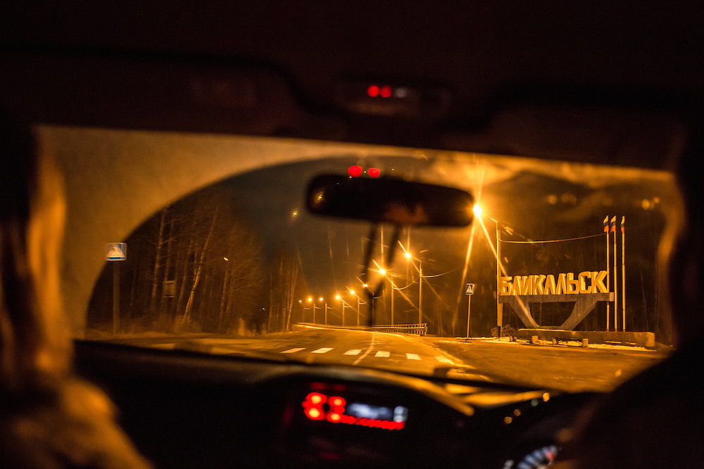 Marina Telezhnikova, left, and Maxim Makarov drive past a sign welcoming visitors to Baikalsk on Saturday, October 19, 2013 in Baikalsk, Russia.