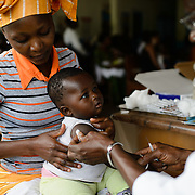 Aly Konate (seven months), pictured with his mother, Mama Diakite (20), being vaccinated against tetanus at a health centre in the village of Guiglo in western Cote d'Ivoire on 13 August 2012.
