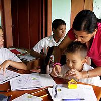 Central America, Costa Rica, Puerto Jiminez. Teacher helps child at Esculea Carbonera, a small school nearby Lapa Rios.
