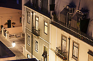 """Hotel """"Casa das janelas com Vista"""" with green tiles on the facade, seen from above with River Tagus and 25th April bridge on the background"""