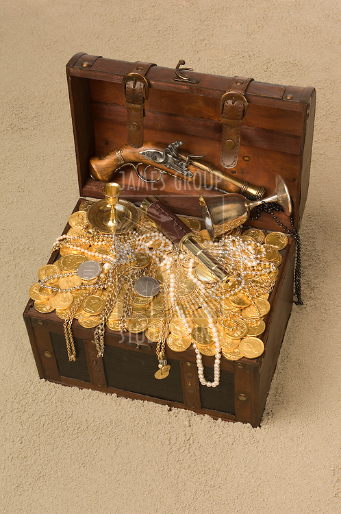 Pirate treasure chest with the lid open brimming with gold coings and pirate paraphernalia on a sandy beach