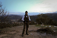 Standing on guard in the early morning along the hillside that overlooks Jisr al-Shugur and Al Janoudiyah, a Free Syrian Army (FSA) soldier protects the surrounding countryside from further attacks by Syrian government forces.