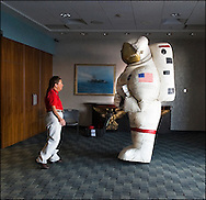 A NASA worker and a man in a giant inflatable spacesuit at the Intrepid