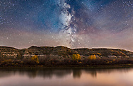 The Milky Way in Sagittarius (toward the galactic centre) going down behind the badland hills along the Red Deer River. I shot this near East Coulee on Highway 10 in Alberta, on an autumn night. Some clouds were drifting through over the exposure times. Passing car headlights helped light the trees on the opposite bank. <br /> <br /> This is a stack of 4 tracked exposures for the sky (each 2 minutes at f/2.2 with the 24mm lens) and then 4 untracked exposures for the ground (each 4 minutes at f/2.5), all with the Canon 6D at ISO 800. The tracker was the iOptron Sky-Tracker. Stacking, using Mean stack mode, helps smooth noise. This was shot as a demo image for use in a video tutorial series.