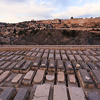Restored graves in the Jewish cemetery on Jerusalem's Mount of Olives. The Jewish Quarter of the Old City of Jerusalem, Temple Mount and Dome of the Rock are visible in the background.