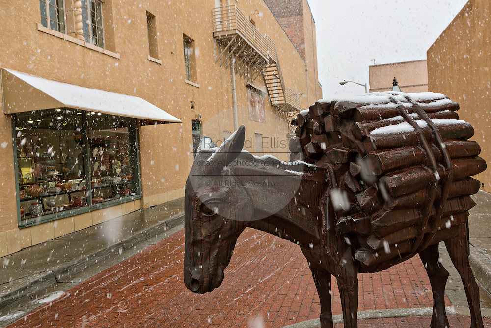 A sculpture of a donkey marks the entry to Burro Alley once known for brothels and saloons in the old west during a winter snow in Santa Fe, New Mexico. Before automobiles almost all goods were transported into the mountain town by pack animals.