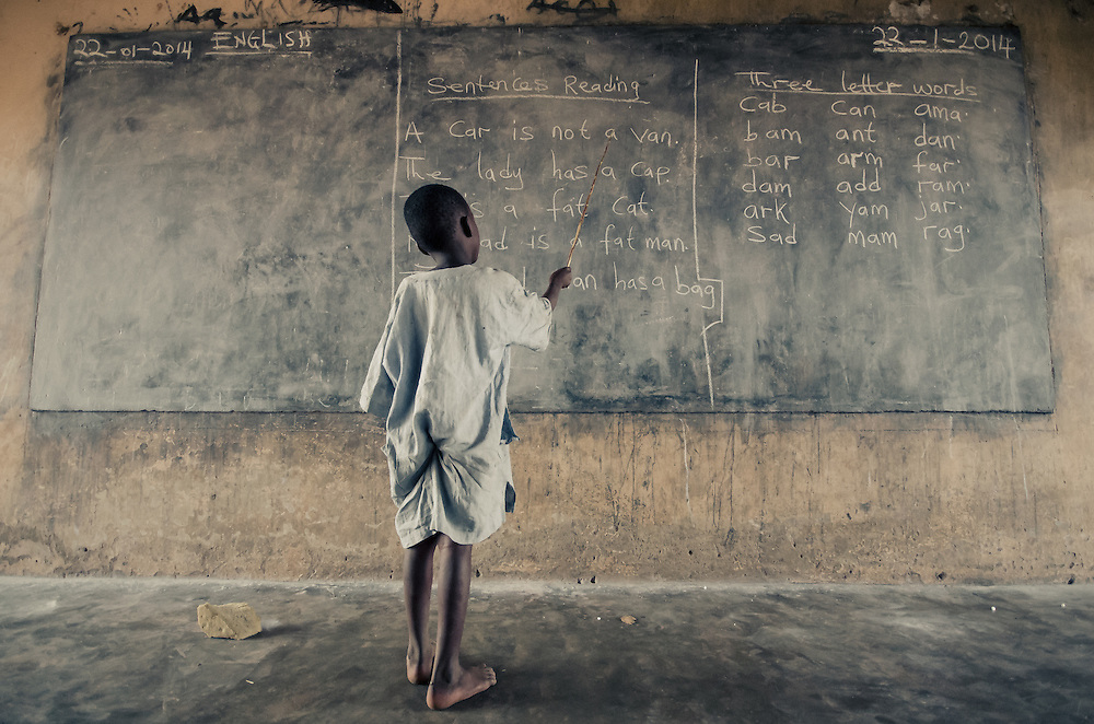 A young boy points at the words on the blackboard as his classmates call them out.