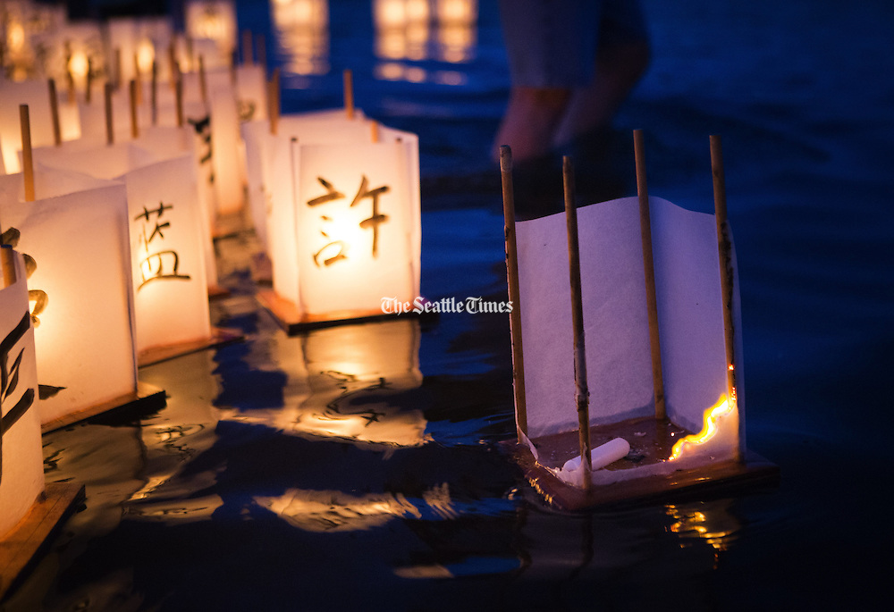 A paper lantern catches fire as it floats out onto the waters of Green Lake during the annual From Hiroshima to Hope event, which observes the anniversary of the Hiroshima and Nagasaki atomic bombings. <br />
