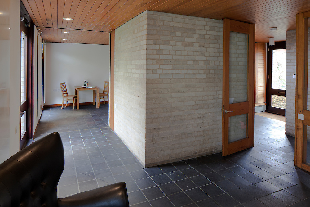 1960s designed house, interior with grey brick walls and wooden clad ceiling