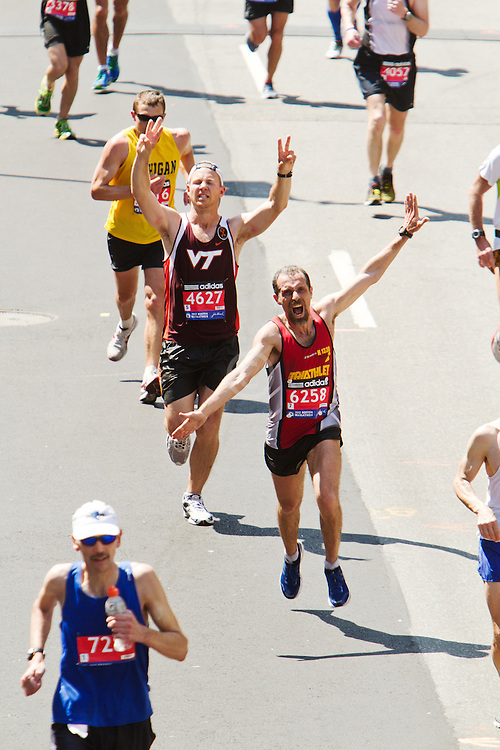 runners steps away from crossing the finish line at Boston Marathon