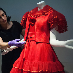 London, UK - 2 April 2014: V&A researcher Lucia makes final adjustments on an Evening Dress, Red Tulle, Valentino 1977 during the press view of the 'The Glamour of Italian Fashion 1945-2014' exhibition at the Victoria & Albert Museum