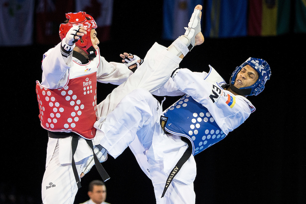 Steven Lopez of the United States kicks Javier Medina of Venezuela during their bronze medal contest in men's taekwondo -80 kg division at the 2015 Pan American Games in Toronto, Canada, July 21,  2015.  AFP PHOTO/GEOFF ROBINS