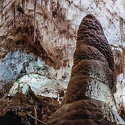 Large column, in Carlsbad Caverns National Park, in the Guadalupe Mountains, Chihuahuan Desert, southeast New Mexico, USA. Hike in on your own via the natural entrance or take an elevator from the visitor center. Geology: 4 to 6 million years ago, an acid bath in the water table slowly dissolved the underground rooms of Carlsbad Caverns, which then drained along with the uplift of the Guadalupe Mountains. The Guadalupe Mountains are the uplifted part of the ancient Capitan Reef which thrived along the edge of an inland sea more than 250 million years ago during Permian time. Carlsbad Caverns National Park protects part of the Capitan Reef, one of the best-preserved, exposed Permian-age fossil reefs in the world. The park's magnificent speleothems (cave formations) are due to rain and snowmelt soaking through soil and limestone rock, dripping into a cave, evaporating and depositing dissolved minerals. Drip-by-drip, over the past million years or so, Carlsbad Cavern has slowly been decorating itself. The slowest drips tend to stay on the ceiling (as stalactites, soda straws, draperies, ribbons or curtains). The faster drips are more likely to decorate the floor (with stalagmites, totem poles, flowstone, rim stone dams, lily pads, shelves, and cave pools). Today, due to the dry desert climate, few speleothems inside any Guadalupe Mountains caves are wet enough to actively grow. Most speleothems inside Carlsbad Cavern would have been much more active during the last ice age-up to around 10,000 years ago, but are now mostly inactive. This panorama was stitched from 6 overlapping photos.