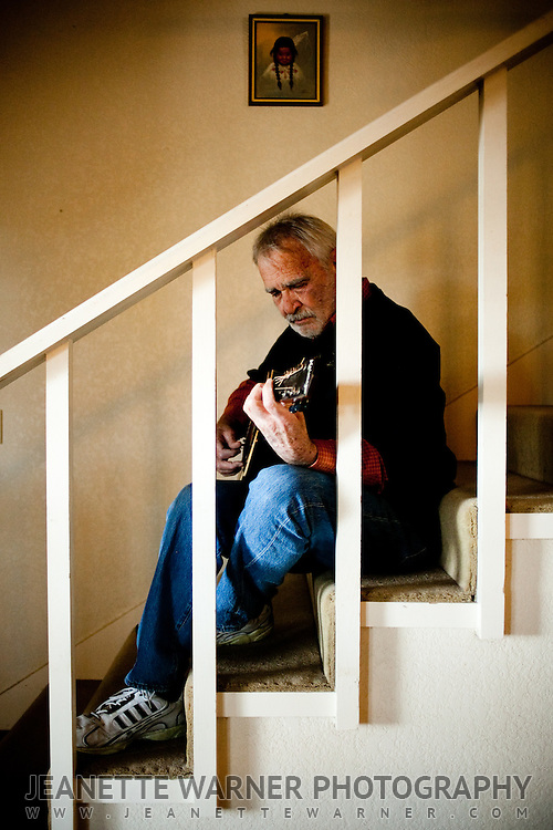 Singer/Songwriter Sonny Throckmorton poses with his guitar in his house in Spicewood, Texas.