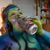 "Gabi Jones drinks a soda during a break from being painted by airbrush artist David Brawner as a piece of ""bodyart"" in a garage studio in a Denver suburb April 13, 2010.  Jones (not her real name) at 502 pounds is a size acceptance advocate who says she wanted to be painted ""...to push the envelope on what a big person can do and break the molds of what is accepted in society.""  REUTERS/Rick Wilking  (UNITED STATES)"