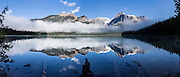 Morning fog breaks to reveal the President Range above Emerald Lake in Yoho National Park, British Columbia, Canada. The Emerald Triangle makes a fine hike of 20 km (12 miles, with 3200 feet gain) around Emerald Lake and over Burgess Pass and Yoho Pass. Yoho is one of several Canadian Rocky Mountains parks which comprise a spectacular World Heritage Area listed by UNESCO in 1984. The panorama was stitched from 6 overlapping images.