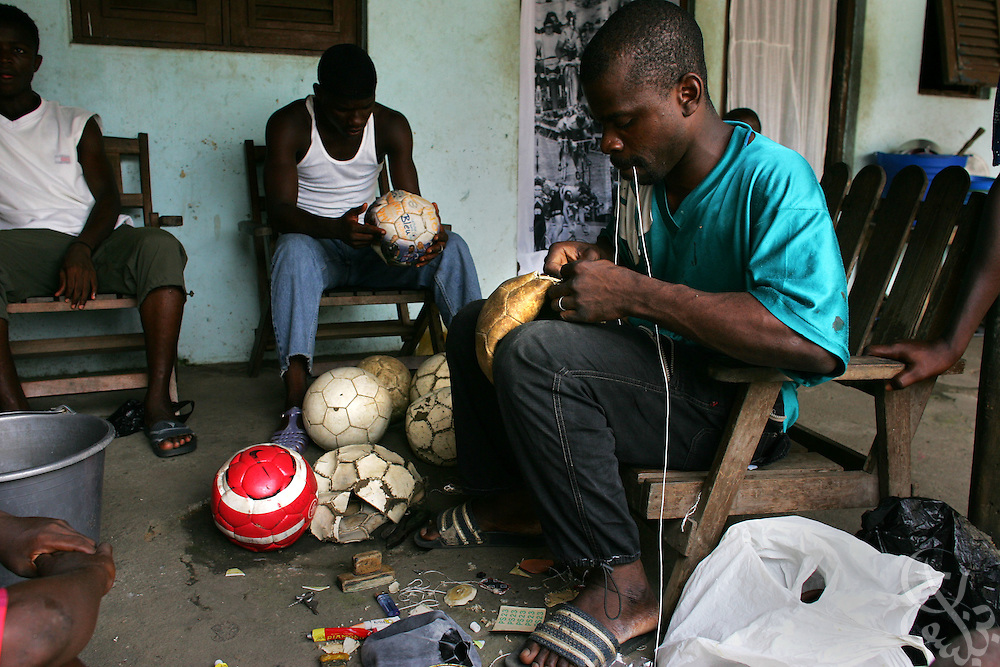 "Blaise N'cho, age 29, repairs footballs in the Abobo neighborhood of Abidjan, Côte d'Ivoire February 19,2006.  N'Cho, a shoe repairman, who's skill at repairing balls has earned him the reverent nickname  ""Le Seigneur"", or ""the Lord"", charges $1 per ball for most repairs and works out of his small family home."