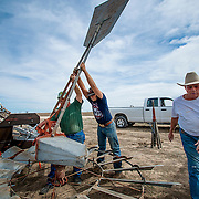 Tommy Houston, right, owner of the Houston Ranch near Bluff Dale in Erath County, Texas, helps Mark Welch, left, and Taylor Rhodes install a windmill. This is the second windmill Houston has added in the past two years, bringing the ranch's total to 14. Welch is owner of The Second Wind, a windmill restoration and installation company in Benbrook, Texas.<br />