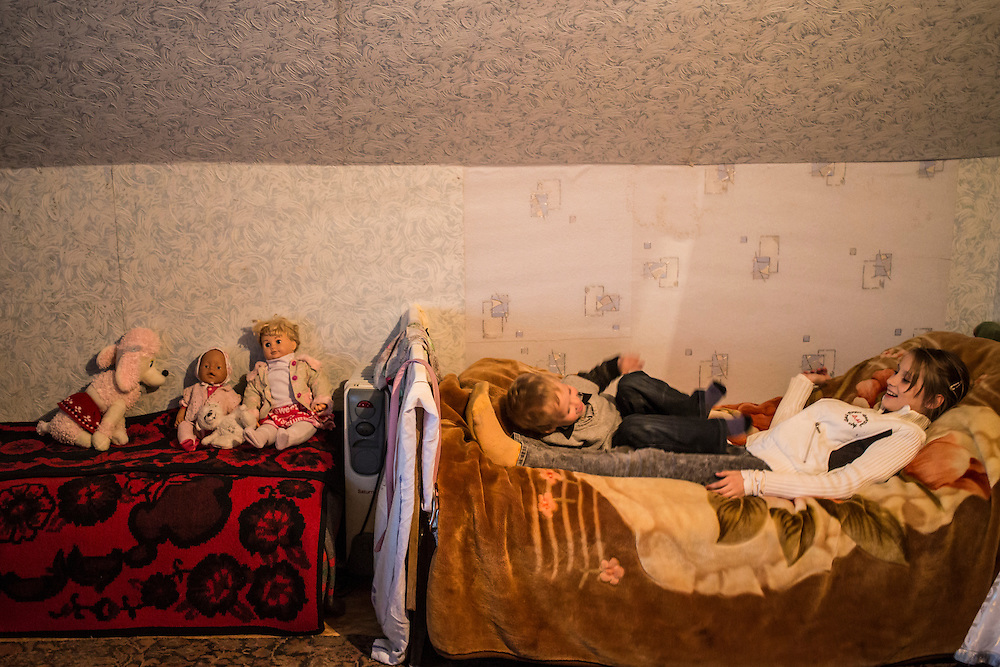 DNIPROPETROVSK, UKRAINE - OCTOBER 12: Yeva (R) and her host brother Ilya play on a bed in the attic where she, her mother, and her grandmother are living with a family in their church's congregation after fleeing fighting in Luhansk in Eastern Ukraine on October 12, 2014 in Dnipropetrovsk, Ukraine. The United Nations has registered more than 360,000 people who have been forced to leave their homes due to fighting in the East, though the true number is believed to be much higher.(Photo by Brendan Hoffman/Getty Images) *** Local Caption ***