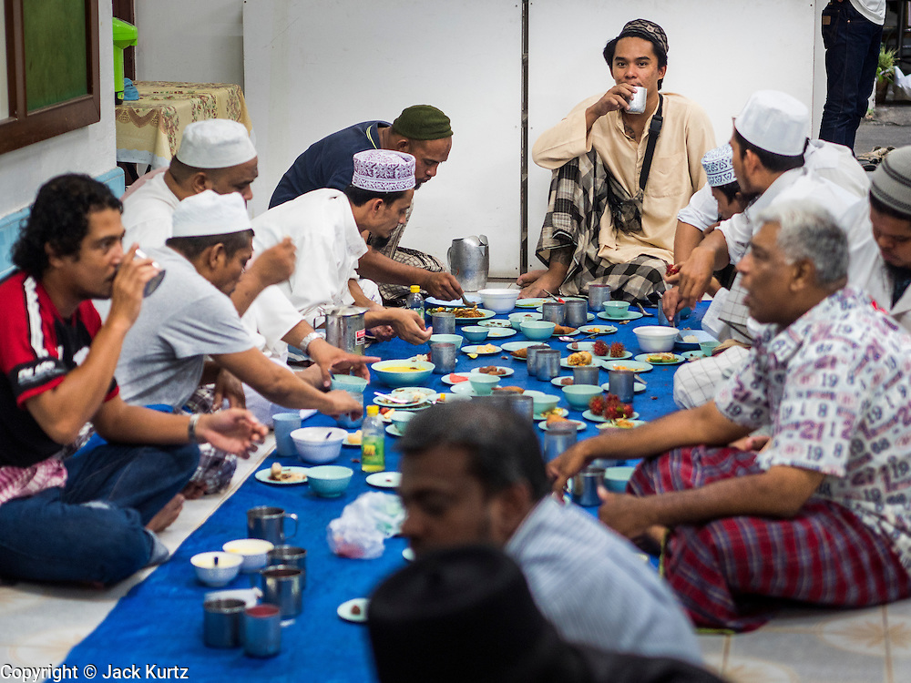 10 JULY 2015 - BANGKOK, THAILAND:  People break the daily Ramadan fast during Iftar at Haroon Mosque in Bangkok. Iftar is the evening meal when Muslims end their daily Ramadan fast at sunset. Iftar is a communal event at Haroon Mosque and hundreds of people usually attend the meal.    PHOTO BY JACK KURTZ
