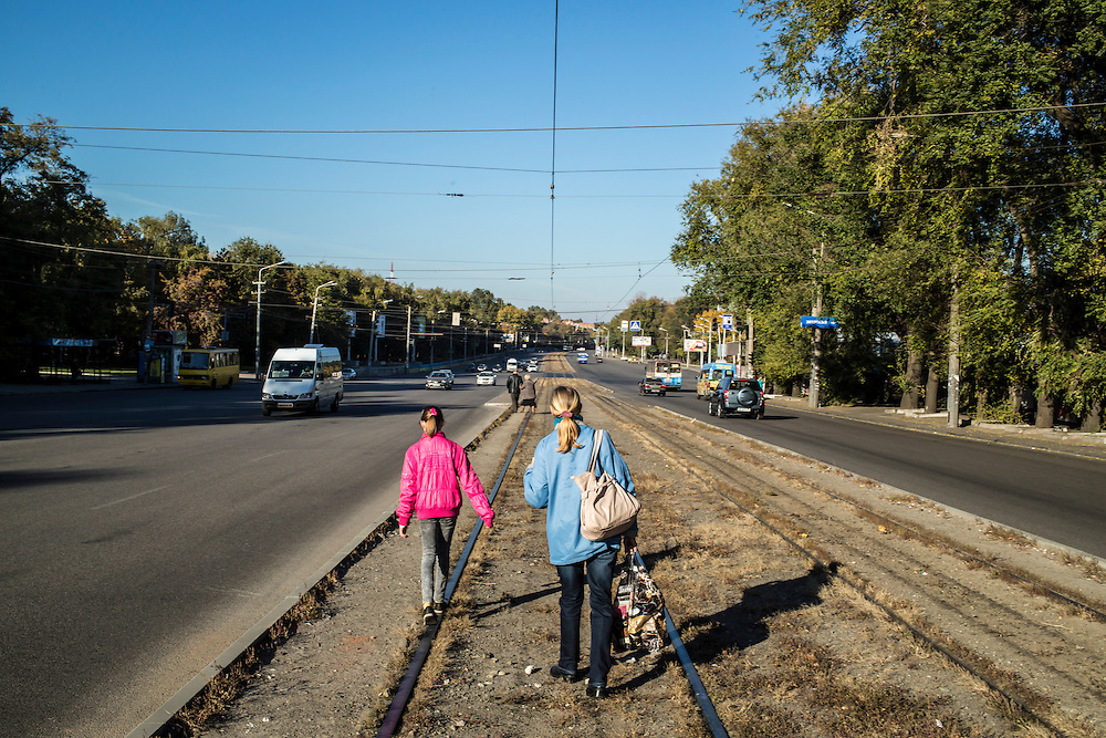 DNIPROPETROVSK, UKRAINE - OCTOBER 12: Yeva, 10, and her grandmother, Svitlana Kostromina, wait for a tram on the long trip from the Good News Evangelical Church to the home where they are living with a family that is part of the congregation on October 12, 2014 in Dnipropetrovsk, Ukraine. Yeva and her family fled fighting in Luhansk. The United Nations has registered more than 360,000 people who have been forced to leave their homes due to fighting in the East, though the true number is believed to be much higher.(Photo by Brendan Hoffman/Getty Images) *** Local Caption *** Svitlana Kostromina