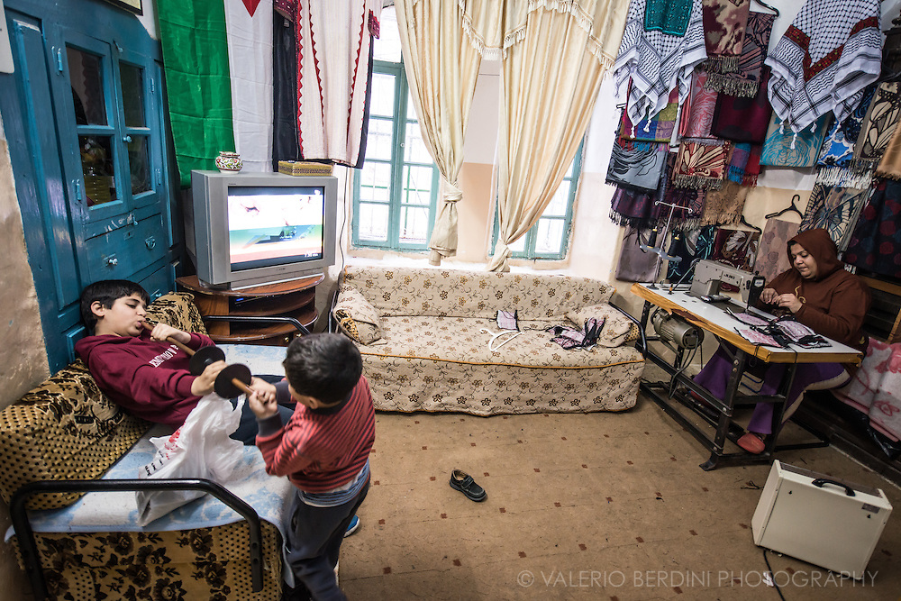 Children play while the mum (of the younger) works at the sewing machine. A snapshot of secluded life in Hebron Area H2. This living room is also the workshop and converts into the children bedroom at night.