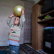 Abd al Latif, 3, plays in his neighbors apartment. He, his parents, and four siblings escaped the Syrian conflict two months ago, and now live in a small two-room apartment where they share a make-shift kitchen with their neighbor. April 2013, A-Sareeh, Jordan.