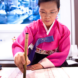 Milan, Italy - February  17: Kumyoungsuk from Korea writes in korean characters at BIT International Tourism Exchange on february 17, 2012 in Milan, Italy.