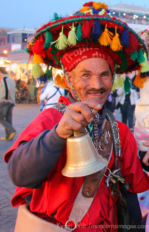 North Africa, Africa, Morocco, Marrakesh. Traditional water carrier wanders the Djeema el Fna ringing a bell and posing for tourists.