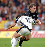 2005/06 Guinness Premiership Rugby, Saracens vs Leeds Tykes,  Sarries Glen Jackson is tackled by Tykes centre Roland de Marigny. Vicarage Road, Watford, ENGLAND: Sunday 11.09.2005.   © Peter Spurrier/Intersport Images - email images@intersport-images..   [Mandatory Credit, Peter Spurier/ Intersport Images].