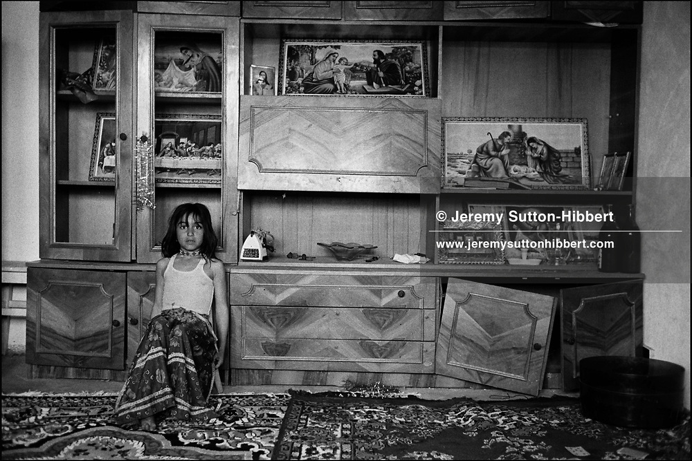 Portocala MIhai, her name Portocala translates as 'orange', sits in front of religious pictures in the living room of her family home, in the Kalderash Roma camp of Sintesti, near Bucharest. The Roma of Sintesti are Romanian Orthodox in religion.