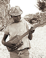 Oke Cherie, okay darling - a boy playing a lively tune on his tin can guitar