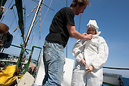 Giorgia Monti of Greenpeace Italy demonstrates wearing nuclear radiation protection clothing suits on board the Greenpeace ship Rainbow Warrior, as it transits northwards to Fukushima, Japan, on Monday 25th April 2011.