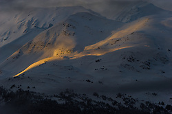A sliver of an early morning sunrise shines on  the slopes of Mount Jonathan Ward outside Haines, Alaska near the Alaska Chilkat Bald Eagle Preserve.
