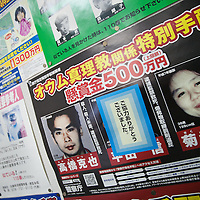 """A police 'wanted' poster for members of Aum Shinrikyo hangs on the wall of a bus station, with the central image covered by a sticker after the suspect, Hirata Makoto, was arrested after surrendering himself at a police station on 31st December 2011. Left to right the criminals are Takahashi Katsuya (left), Hirata Makoto (centre), Kikuchi Naoko (right). Takahashi and Kikuchi are """"wanted"""" for taking part in the 1995 Tokyo underground sarin gas attack by Aum Shinrikyo Supreme Truth Cult. Photographed in Fukura, Awajishima, Japan, on Wednesday 11th January 2012."""