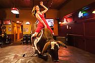 Woman, mechanical bucking bull, riding, Livingston, Montana, MODEL RELEASED