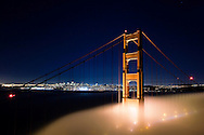 A foggy view of the Golden Gate Bridge and San Francisco with a clear sky above.
