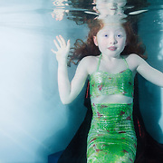 Little girl in green mermaid's costume sitting in the corner of a pool underwater, startled with her hands up.