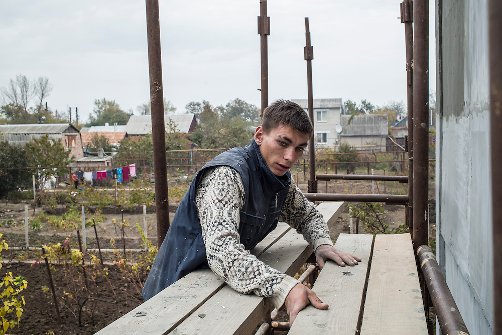 Vitaliy Kondratovich, 19, at his construction job on Wednesday, October 15, 2014 in Berdyansk, Ukraine. An orphan, Kondratovich walked nearly 200 kilometers from Donetsk to Berdyansk to escape fighting and the possibility of being drafted into a rebel militia, where he was helped by local businessman Oleg Zinchenko. Photo by Brendan Hoffman, Freelance