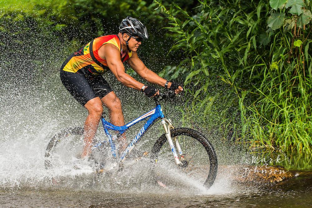 Speeding mountain biker splashing through a stream, Kauai, Hawaii