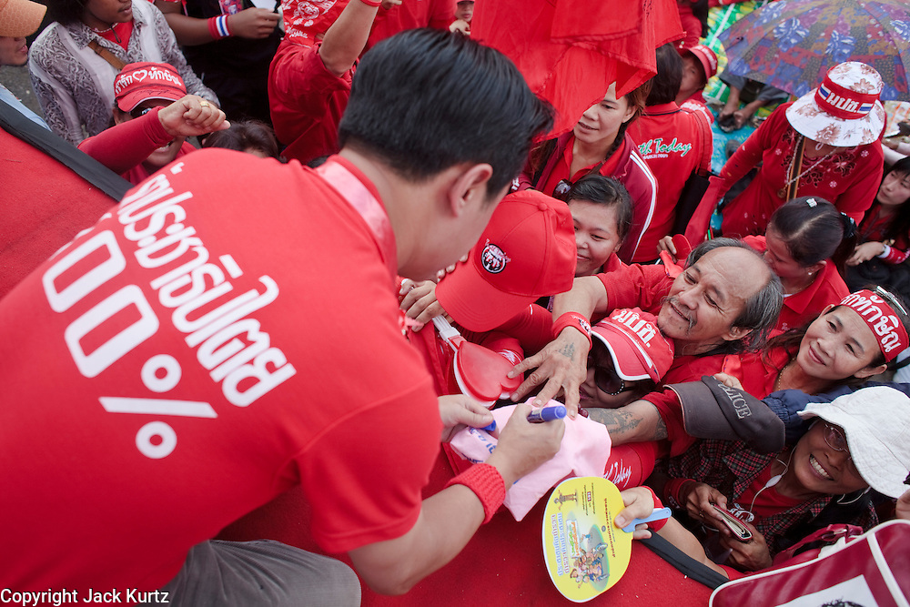 "Mar. 26, 2009 -- BANGKOK, THAILAND: JAKRAPOB PENKAIR, former spokesman for ousted Thai Prime Minister Thaksin Shinawatra signs autographs during an anti-government rally in Bangkok Thursday. More than 30,000 members of the United Front of Democracy Against Dictatorship (UDD), also known as the ""Red Shirts""  and their supporters descended on central Bangkok Thursday to protest against and demand the resignation of current Thai Prime Minister Abhisit Vejjajiva and his government. Abhisit was not at Government House Thursday. The protest is a continuation of protests the Red Shirts have been holding across Thailand in March.  Photo by Jack Kurtz"